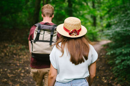 Couple holding hands walking in forest, back view. Adventure, travel, tourism, hike, people. Rear view of two people carrying backpack while walking through wood. Man holds girlfriend by hand on hike.