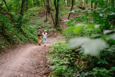Happy caucasian couple are walking in a dense forest along the path holding hands, rear view. Hikers with backpack looking for place for picnic in wooded area in the summer. Walk outdoors together. 免版税图像