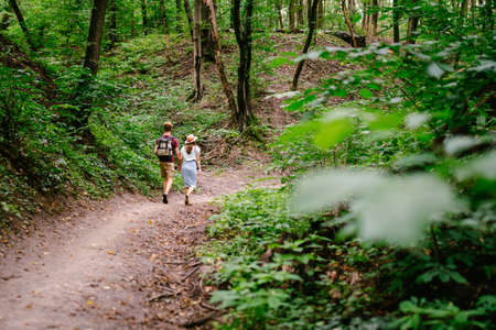 Guy and girl walk together in wood along the trail, holding hands. Back view. Happy couple holding hands and walking forest path. Hikers walk in wooded area with a backpack in summer. 免版税图像