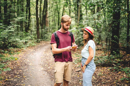 Hikers using mobile gps for directions. Happy couple checking smartphone in the woods during backpacking trip. Young joyful couple using gps map, navigator geolocation app. love and travel concept.