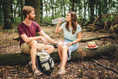 Hikers taking break during woodland walk. Young caucasian man and woman sit on fallen tree and drinking water from plastic transparent bottle. Couple traveler drink water in the forest.