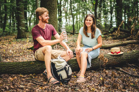 Couple relaxing sitting on a log and drinking water. The family is enjoying a romantic weekend in nature. A pleasant walk or a romantic date in the background of nature. Picnic hike in the forest. Banco de Imagens