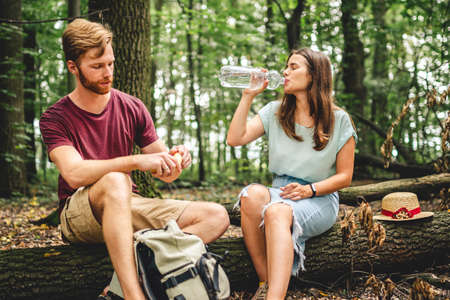 Caucasian couple stopped to rest while walking in the forest, young people sit on a fallen tree trunk drinking water from a bottle. Active rest, hike in a wooded area. Thirst and water balance. Banco de Imagens