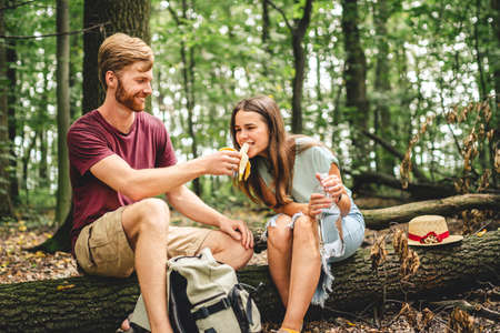 People eat banana and drink water from plastic bottle while sitting on log in wood. Couple hikers take break for food and drink in forest on fallen tree trunk. Stop for picnic, trail forest walk.