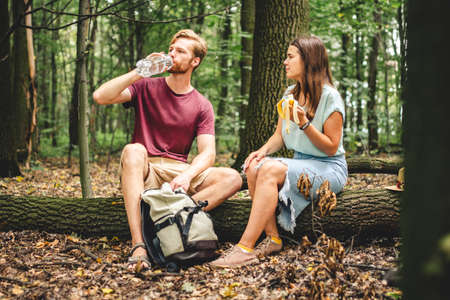 young couple sat to rest during forest walk along path to fallen tree, people drink water and eat banana fruit. Tourists break for snacks and replenishment water balance. Food and drinks in nature.