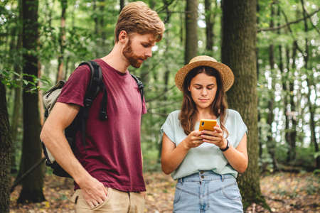 Couple hiking and using maps app on cell phone. Two people hikers looking at mobile phone trying find route. Hike in forest, looking smartphone, search tourist attraction, adventure travel concept.