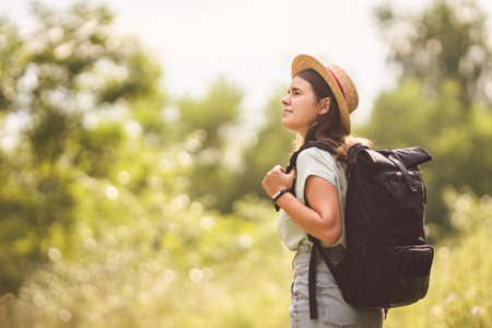 Stylish fashionable hipster traveler woman in hat with brim and roll top type backpack walking in nature. Travel and wanderlust concept. Exploring nature, hot summer day. Outdoor activity. Wanderlust.