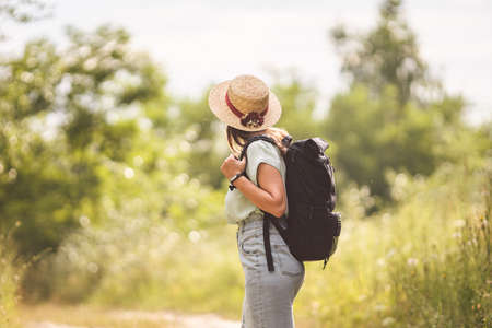 Stylish hipster girl in straw hat traveling countryside. Young woman with backpack exploring and walking in summer nature park. Travel concept and wanderlust. Woman hiker enjoying amazing landscapes. 免版税图像