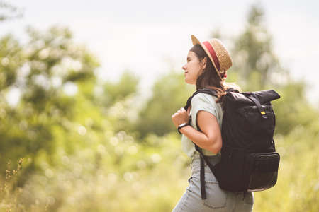 Young travel girl at viewpoint. Hipster girl with backpack. Travel concept. Beautiful woman hiker enjoying amazing landscapes. Holiday vacation and freedom. Back view. Traveler Walking In Nature. Banco de Imagens