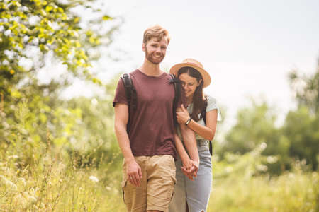 Caucasian hipster couple walking along path in countryside. man with beard holds the hand of his beloved girl while hiking in natural park with backpack. Travel, hiking, tourism and people concept.