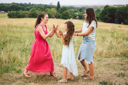 Fun active family weekend in nature. Happy young mother with two daughters is having fun in field outside the city. Three adult sisters in dresses on vacation in the countryside. Three young friends. 版權商用圖片