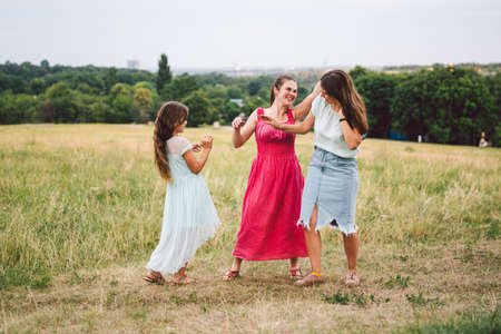 Three adult Caucasian sisters are playing and having fun on the field. A family of three young women laugh and spend summer time in nature. Happy child, mom and sister run and play outdoors.