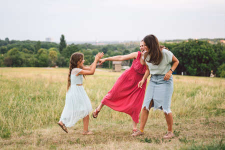 Three sister girls playing on the park outdoor. 3 girls, sisters, girlfriends in the field. Happy mother with younger and older daughter, two children plays in the meadow in summer in dresses.