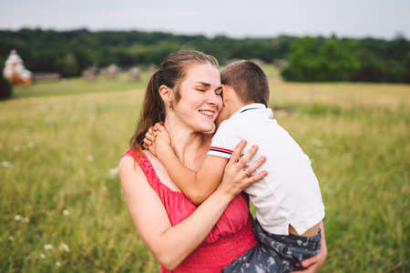 Young caucasian mother holds in her arms hugs and hugs her son in nature in summer. Motherhood and family happiness. A single mother and her child have fun together. Mom and son hugging. Фото со стока