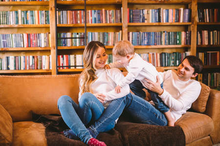 Lovely family with baby son dressed in the same clothes have fun on sofa at home during Christmas. Family Christmas Concept. Happy parents with cute child In a living room on new year holidays.