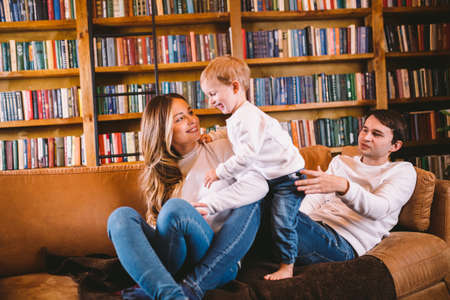 Christmas family portrait. Young Caucasian family in identical clothes having fun on sofa in living room with large library of books and Christmas tree in evening. Happy New Year and Merry Christmas. Standard-Bild