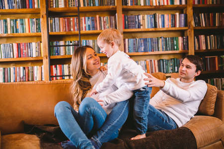 Happy parents playing with small child at Christmas time at home in living room on sofa near large cabinet with books and Christmas tree in evening. Family holiday in winter new year and christmas. Standard-Bild