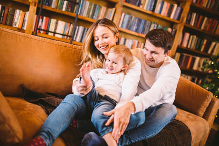 Happy family on sofa near bookcase and Christmas tree in evening. Cozy family atmosphere at christmas time . Enjoyng love hugs, holidays people. Togetherness concept. Home holiday living room.
