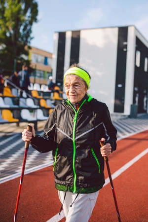 Senior woman walking with walking poles in stadium on a red rubber cover. Elderly woman 88 years old doing Nordic walking exercises at the city stadium on the running track. Healthy lifestyle concept.