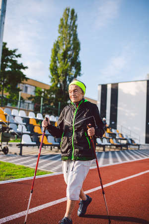 Active rest of the elderly theme. Sports and health in retirement. Caucasian very old woman with deep wrinkles doing Nordic walking exercises with sticks outside in the city stadium.