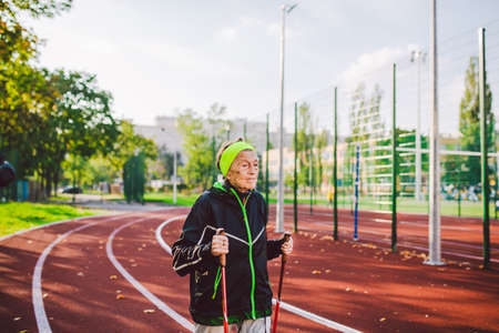 Old woman in sportswear practicing nordic walking outdoors on rubber treadmill in stadium. Older female walk by scandinavian walk use trekking sticks and nordic poles. Retired people healthy lifestyle. Standard-Bild