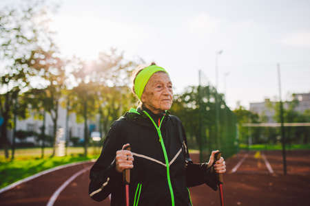 Active elderly Caucasian elderly women of 90 years practice Nordic walking with ski poles on a track with a red rubber coating. Active holidays. A fit woman. Healthy lifestyle for the elderly.