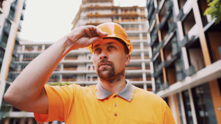 Serious Caucasian builder stands at construction site puts on orange hard hat. Safety first of all, construction profession. Low angle shot. Foreman inspects construction progress, putting on helmet.