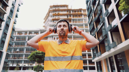 Construction worker with ear muff working at construction site. Worker puts on ear defenders to protect against sound. Taking care of health, safety at work. Earplugs. Too loud sound, hearing damage.