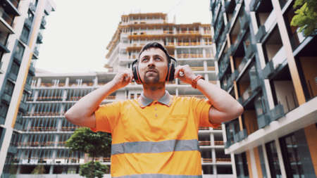 Builder covers his ears, ear muff to protect workers ears. Construction worker wearing protective ear defenders. Concept of construction, taking care of safety during work. Protection against injury.