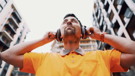 Man wearing safety equipment hearing protection. Worker wearing noise cancelling ear defenders or ear muffs. Construction builder puts on protect ears with headphones. Taking care safety during work.
