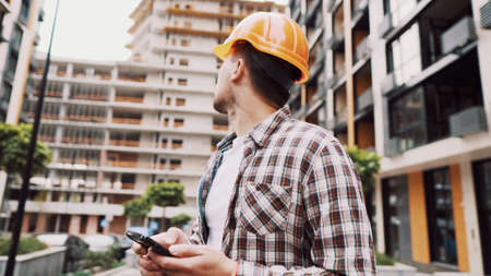 Caucasian male construction worker in protective helmet use smartphone near building that is being built. Engineer checks construction process, makes notes on phone. Foreman chatting in application.