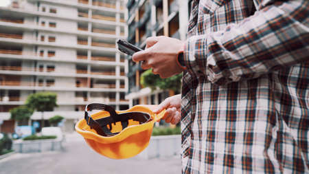 Young Engineer using smartphone on construction site. Architect using phone. Manager development building texting on smart phone. Builder makes notes in application during inspection and verification.