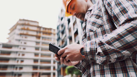 Inclusion of mobile applications in the development management process. Caucasian engineer builder in hard hat use on construction site mobile phone, engineer at work checking building project.