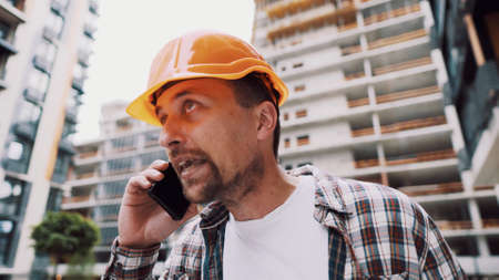 Engineer talking on phone. Architect using phone on construction site. Foreman phone call control process. Construction worker communications in construction industry. Building professional phone.