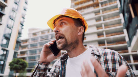Angry builder, dissatisfied with deadline of work, swears at stress while talking to foreman on phone background of construction site. Wrathful architect, construction engineer talking on cell phone.