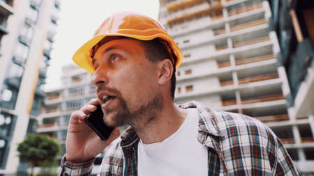 Angry male architect in orange hard hat talks swears on phone at construction site. Builder in plaid shirt emotionally displeased negotiates by cell phone. Screaming stressed architectural designer.