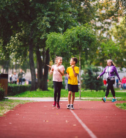 Kids run. Healthy sport. Child sport, heterosexual twins running on track, fitness. Joint training. Running training outdoor brother and sister pre-teen. Jogging with friend. Children athletes.
