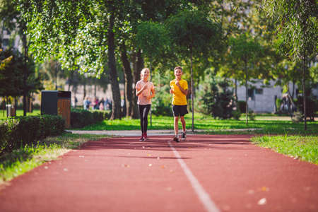 Couple of kids boy and girl doing cardio workout, jogging in park on jogging track red. Cute twins runing together. Run children, young athletes. Teen brother and sister running along path outdoors.