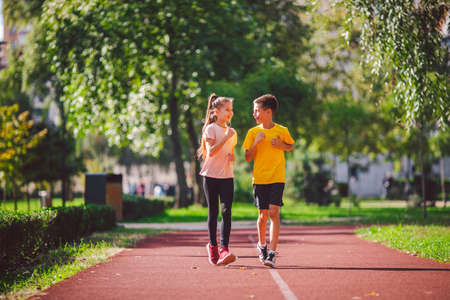 Sports and fitness in adolescence. Caucasian twins boy and girl run on the jogging track in the city park. Two children brother and sister for 10 years running on a rubberized outdoor treadmill. Stockfoto