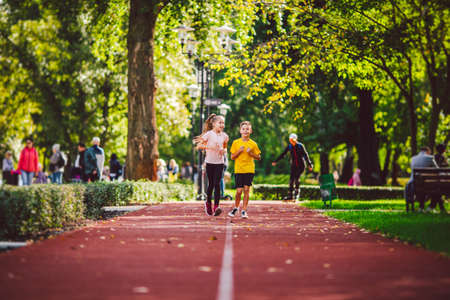 Active recreation and sports children in pre-adolescence. Caucasian twins boy and girl 10 years old jogging on red rubber track through park. Children brother and sister running on treadmill outside.