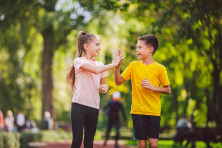 Sports and fitness in adolescence. Caucasian twins boy and girl run on the jogging track in the city park. Two children brother and sister for 10 years running on a rubberized outdoor treadmill.