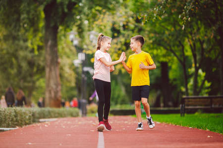 Child fitness, twins kids running on stadium track in city park , training and children sport healthy lifestyle. Outdoor activities by running make the childs body healthy and experience enriched. Stockfoto