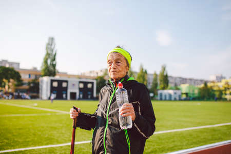 Senior woman practicing nordic walking at city stadium and stopped to quench thirst, drink water from bottle. Age, maturity, active lifestyle and wellness. Joyful retired woman with walking poles.