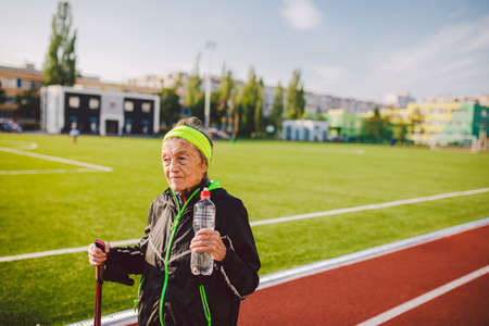 Old woman walking with nordic walk sticks on running track, rubber treadmill and stopped to quench thirst, drink water from a flask. Active female senior. Active retirement, healthy lifestyle concept.