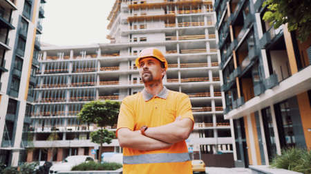 Young caucasian constructor with arms crossed in safety helmet and orange reflective uniform posing with proud expression at construction site. Proud worker posing on building site. Worker portrait. Stockfoto