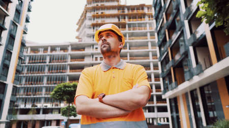 Builder portrait with proud expression. Successful constructor or architect with crossed arms. Construction worker standing with arms crossed in a construction site. Professional building supervisor. Stockfoto
