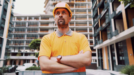 Proud serious young architect or engineer young man with crossed arms as a concept of professional construction supervision outdoors at construction site. Portrait of a serious male builder.