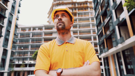 Builder portrait with proud expression. Successful constructor or architect with crossed arms. Construction worker standing with arms crossed in a construction site. Professional building supervisor.