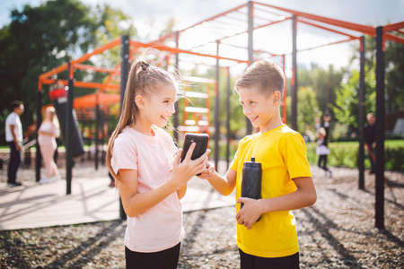 Technology and sport for children. Two teenage kids using smartphone and online workout app. Twins boy and girl watching video on phone during break from sports lesson at school at outside gym.