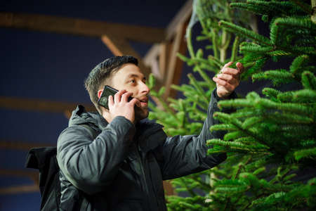 Festive shopping, selection and purchase of New Years attributes. Caucasian man speaks on phone and advises on choosing Christmas tree on evening of New Year Eve. Male buys spruce and uses smartphone.